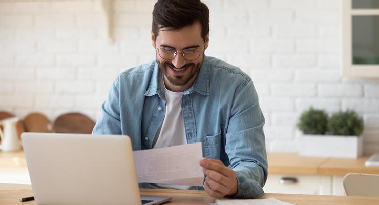 Illustrasjonsfoto. Smilende mann som leser dokument.