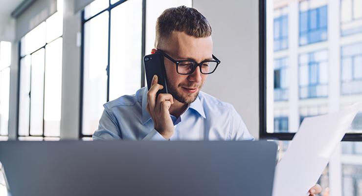 Mann foran bærbar bc som snakker i telefonen og leser på et ark.