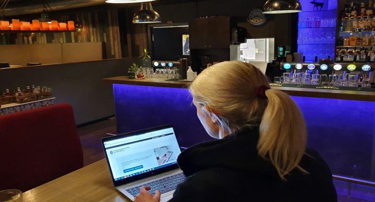 Illustrasjonsfoto. Kvinne foran pc som er inne på www.kompensasjonsordning.brreg.no