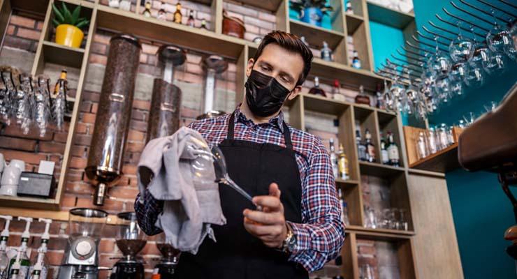 Illustrasjonsfoto. Mann med munnbind rengjør vinglass i en bar.