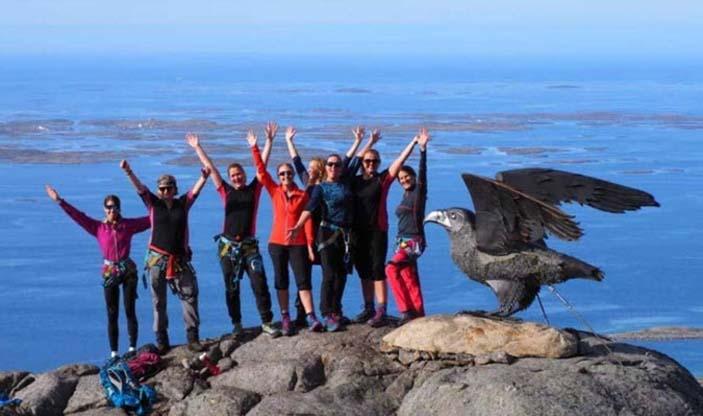 Foto av smilende mennesker med hendene i været på toppen av Ravnfloget, et fjell i Vega kommune.