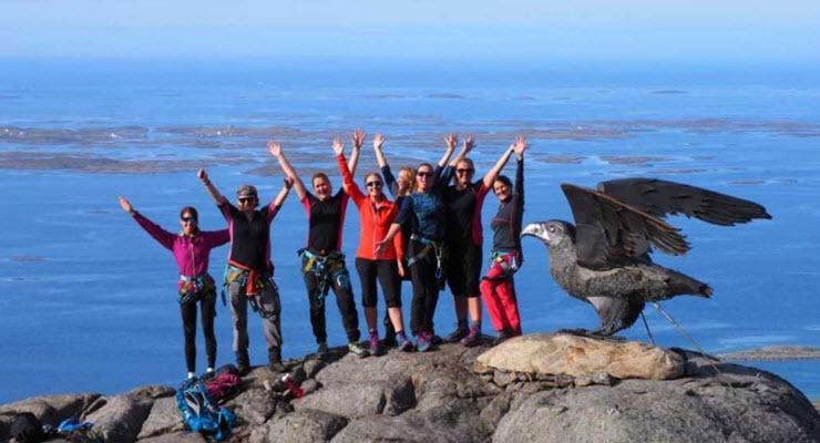 Bilde av smilende mennesker med hendene i været på toppen av Ravnfloget, et fjell i Vega kommune.