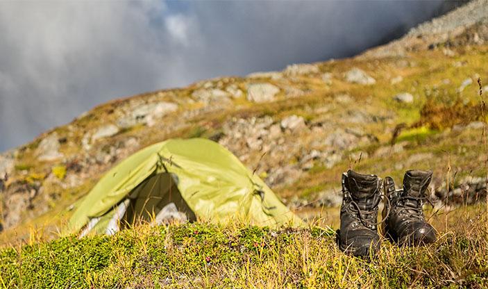 Fjellsko foran telt i fjellet. Bilde