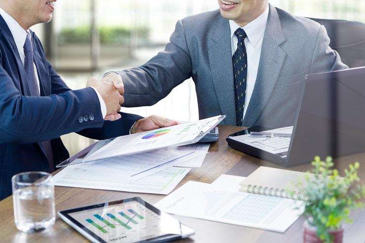 To menn tar hverandre i hånden, gratulerer med avtale.