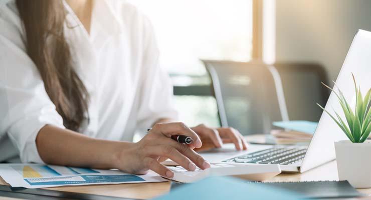 Illustrasjonfoto av kvinnelig regnskapsfører som bruker kalkulator og pc.