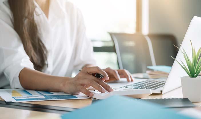 Illustrasjonsfoto av kvinnelig regnskapsfører som bruker kalkulator og pc.