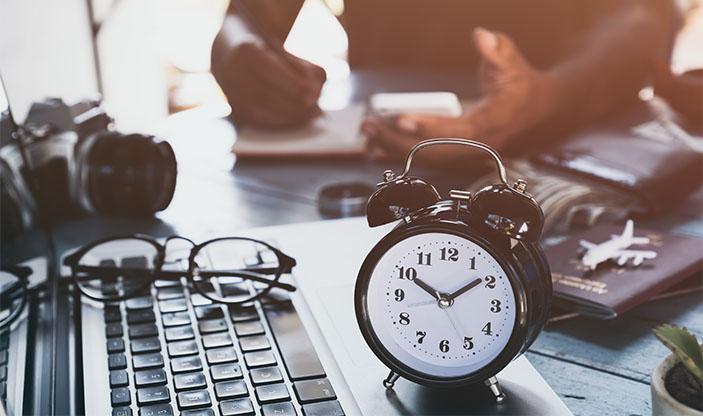mann som jobber, klokke som viser tiden, pc. Foto